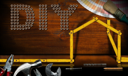 Screws in the shape of text Diy (Do it yourself), wooden folding ruler in the shape of a house with work tools - Home improvement concept