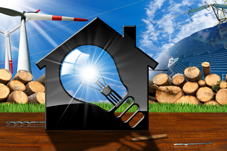 3D illustration of a model house with a light bulb, solar panel, wind turbines, tree trunks and a power line on a wooden table and blue sky - Renewable resources concept Stock Photo