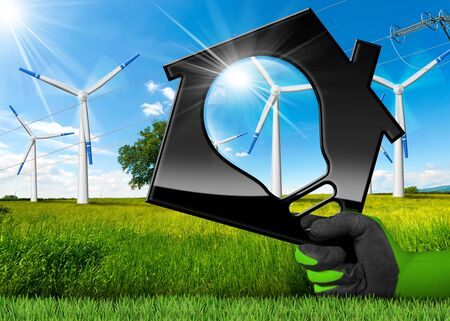 Hand with work glove holding a 3D illustration of a house with a light bulb, wind turbines and a power line on a blue sky with clouds and green grass - Renewable energy concept