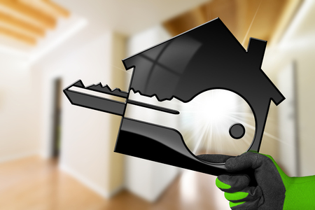 Hand with work glove holding a model house with a key (3D illustration) in a blurred living room. Construction industry concept