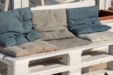Sofa made of white wooden pallet and cushions of cloth. Outdoor setting