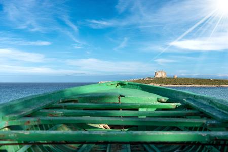 Green wooden boat of migrants and Mediterranean Sea in Portopalo di Capo Passero, Sicily island, Syracuse, Italy, south Europe