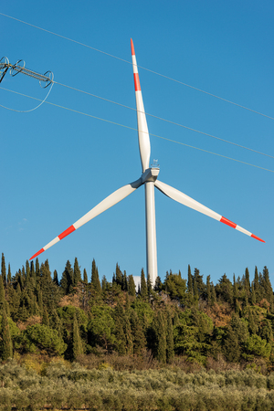 Red and white wind turbine with a power line on a clear blue sky. Renewable energy concept Stockfoto