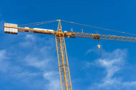 Yellow and orange crane and blue sky with clouds in a construction work site