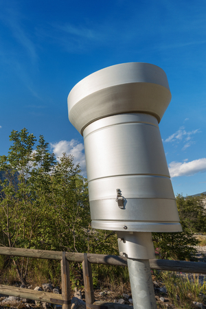 Weather station with metallic rain gauge on a blue sky with clouds