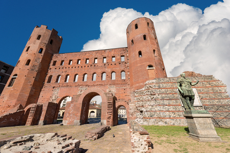 Ancient Roman ruins of Palatine Towers (Porta Palatina) in Turin, Piedmont, Italy and the statue of Julius Caesar