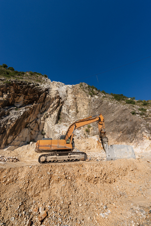 Orange tracker excavator with the jackhammer in a marble quarry (Carrara white marble) in the Apuan Alps (Alpi Apuane). Tuscany, (Toscana), Italy, Europe