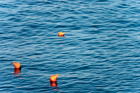 Three orange buoys for mooring boats on the surface of the water. Mediterranean sea, Italy Imagens