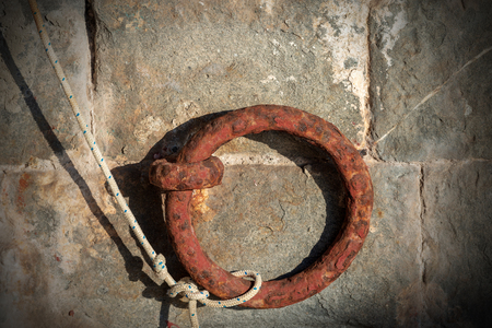 Close-up of a rusty mooring ring with a white and blue rope on a wall in a port, Liguria, Italy Stock Photo