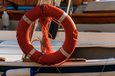 Close-up of an orange and white lifebuoy with ropes hanging on the side of a small boat