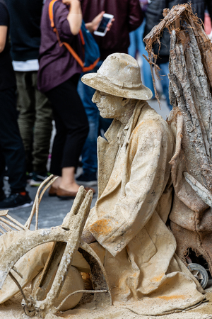 MUNICH, GERMANY - SEPT 7, 2018: A street artist performs (living statue) covered with dried mud, as if it were in a desert. Marienplatz, the central square of Munich
