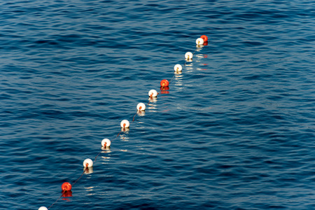 A row of orange and white buoys on the surface of the water, Mediterranean sea, Italy Stockfoto