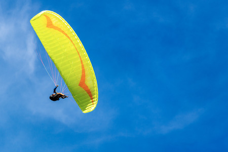 Yellow and orange paragliding on a blue sky with clouds on background
