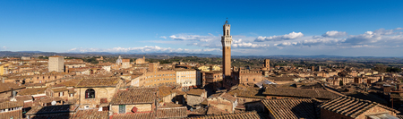 Cityscape of Siena with the Torre del Mangia 87 m. (Tower of Mangia) on blue sky with clouds. Toscana (Tuscany), Italy, Europe