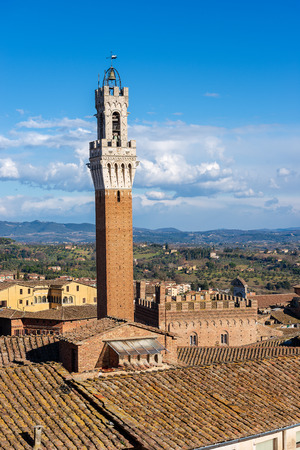 Torre del Mangia 87 m. (Tower of Mangia) on blue sky with clouds. Siena, Toscana (Tuscany), Italy