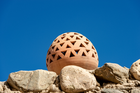 Close-up of a brown clay lamp on a pebble wall with a clear blue sky - Marsa Alam, Egypt, Africa