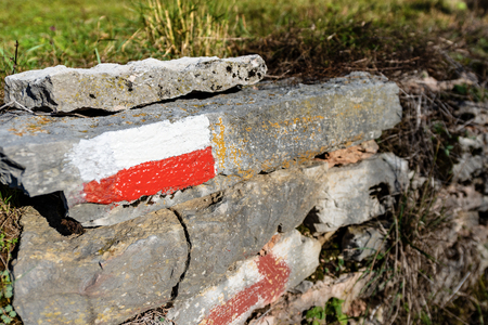 Close-up of a red and white trail Sign on a Rock in Mountain. Hiking trail sign, symbol in Italy alps Фото со стока