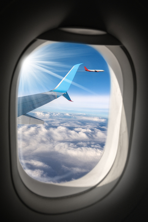 Two commercial airplanes (aircraft wing and plane) photographed through the porthole window