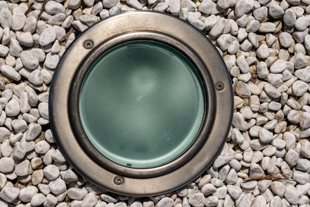 Detail of a lamp on the ground with small white pebbles, outdoor lighting for sidewalk