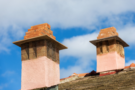 Detail of two chimneys on the top of a house roof on blue sky with clouds - Italy Foto de archivo