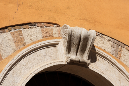 Detail of an old stone arch with ancient keystone on an orange wall. Verona, Veneto, Italy, Europe Фото со стока