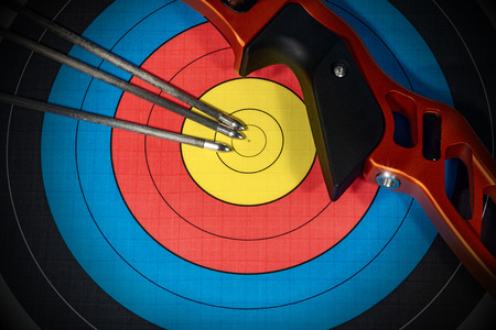 Closeup of a target with three arrows and a bow