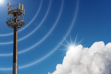 Torre de antena de telecomunicaciones para radio, televisión y telefonía en el cielo azul con nubes y rayos de sol