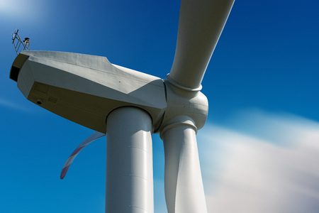 Close-up of a white wind turbine on a blue sky - Renewable energy concept