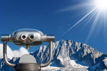 Coin operated electronic binoculars for tourists on a blurred landscape, mountain peak with glacier and blue sky with sun rays