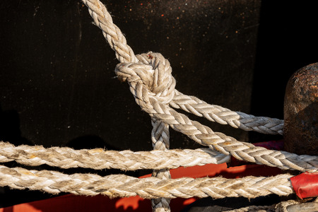 Ropes or hawsers on the quay of the port tied to a mooring bollard