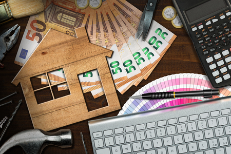 Home improvement concept - Wooden model house with work tools, calculator, banknotes and coins on a wooden desk Stock Photo
