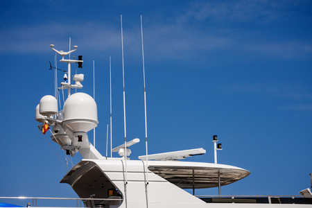 Detail of a luxury white yacht with navigation equipment, radar and antennas on blue sky, superstructure Stock Photo