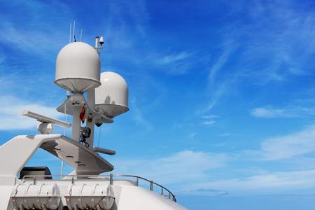 Detalle de un yate de lujo blanco con equipo de navegación, radar y antenas en el cielo azul, superestructura