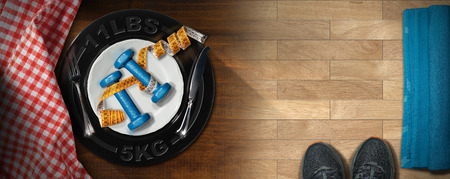 Diet concept - Two dumbbells and a tape measure in a white dish with cutlery on a wooden table with gym parquet, checkered tablecloth, sneakers and towel