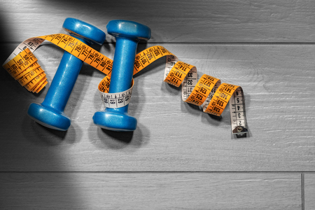 Two small blue dumbbells for women for workout or fitness (free weights) and a orange tape measure on a grey gym floor with copy space Stock Photo