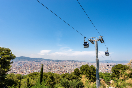 Overhead cable car from Barcelona to the Montjuic hill. In the background the city seen from above. Catalonia, Spain, Europe