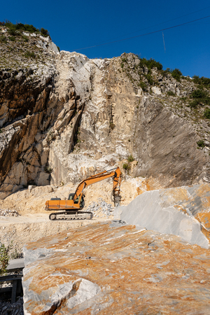 Orange tracked excavator with the jackhammer in a quarry, Carrara white marble in the Apuan Alps Reklamní fotografie