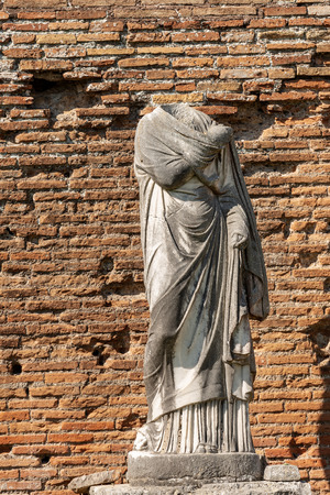 Ancient marble roman statue without head and toga in Ostia Antica, colony founded in the 7th century BC.