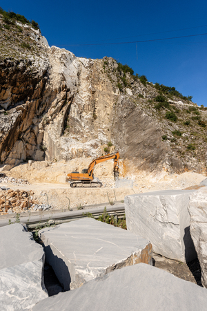 Orange tracked excavator with the jackhammer in a quarry, Carrara white marble in the Apuan Alps (Alpi Apuane - Italian).
