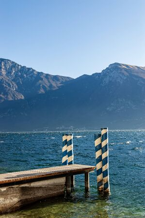 Lake Garda with a small wooden jetty, in the background the Baldo mountain. Beach of the village of Limone sul Garda, Lombardy and Veneto, Italy, Europe