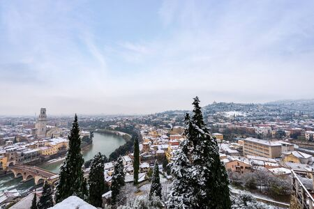 Verona cityscape in winter with snow (UNESCO world heritage site). To the left the river Adige with the Ponte Pietra (Stone bridge) and the cathedral, Veneto, Italy, Europe