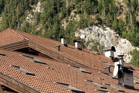 Close-up of a house roof with tiles, skylights and chimneys in mountain, Italian Alps, Trentino Alto Adige, Italy, Europe