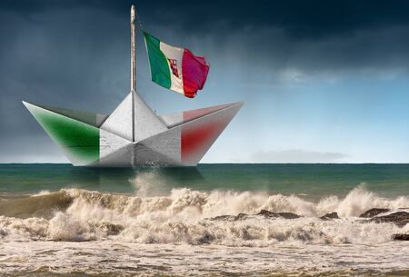 White paper boat with the Italian flag, in a rough sea with wave and sky with rain, photography 스톡 콘텐츠