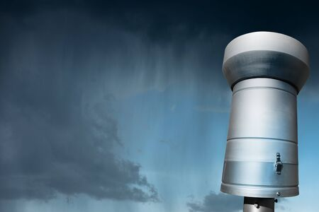 Close-up of a weather station with a metallic rain gauge or pluviometer with rainy sky in the background