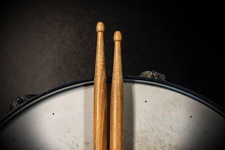Close-up of two wooden drumsticks on an old metallic snare drum with dark background. Percussion instrument