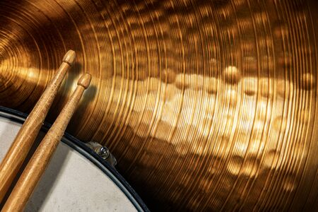Close-up of two wooden drumsticks on an old metallic snare drum and golden colored cymbal with copy space. Percussion instrument