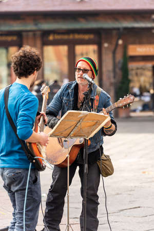 Bologna, Emilia-Romagna, Italy, - Feb 23th, 2020: Two unidentified street musicians play the guitar and sing to entertain people who walking in Piazza Maggiore, Bologna downtown, Emilia-Romagna, Italy, Europe