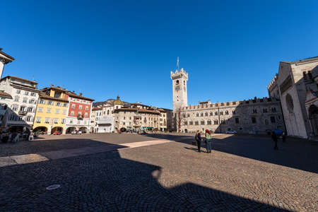 TRENTO, TRENTINO ALTO ADIGE, ITALY - MARCH 8th, 2020: Piazza del Duomo, Cathedral square in Trento city with the Neptune fountain, Civic tower, Praetorian Palace and the frescoed houses Cazuffi Rella.
