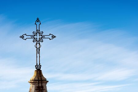 Closeup of an ancient Christian cross in wrought iron on a blue sky with clouds and copy space. Metropolitan Cathedral of San Pietro (910 - XVIII century), Bologna, Emilia-Romagna, Italy, Europe Standard-Bild