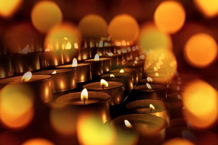 Close-up of a group of votive candles, tea lights, with bokeh effect. Warm background